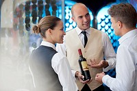 Waiters discussing bottle of wine in restaurant