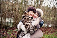 Smiling women hugging in forest