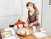 Girl serving brother lunch at table