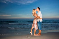 Young couple kissing near the ocean