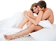 Beautiful pair lays in bed on white