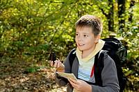 Smiling boy orienteering in forest