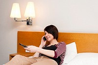 Young woman teenager sitting on bed watching TV and talking on mobile phone
