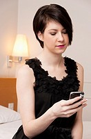 Pretty girl in little black dress texting on mobile phone