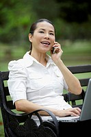 Mid adult businesswoman talking on the phone while working