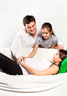 Young pregnant family relaxing on the sofa