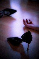 Lifeless body and high heeled shoes at a murder scene
