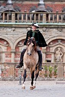 Frederiksborger. Dun stallion with rider in historic costume performing a passage in front of Frederiksborg Palace, Danmark
