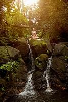Pacific Islander woman practicing yoga on rocky waterfall
