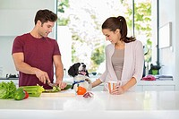 Dog with couple cooking in kitchen