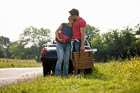 A young couple standing in front of a black sports car with a picnic basket
