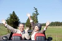 middle aged couple spreading arms in front seats of a car