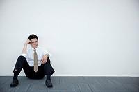 a distressed businessman sitting against wall
