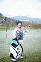 a woman with a golf club at a golf course