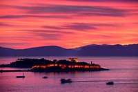 Red sky sunset at Kusadasi Turkey Harbour with lit Guvercin Adasi Island Genoese castle on the Aegean Sea with mountains of Samos Greece