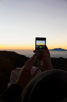 Indonesia, Human hand taking photo of sunrise