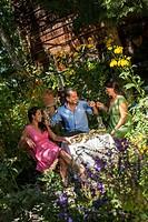 Austria, Salzburg Country, Family dining in garden, smiling