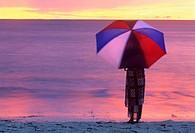 woman with an umbrella on a beach of Denis island, Republic of Seychelles, Indian Ocean