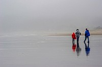 Family walking on rainy day on Cannon Beach.Cannon Beach,Oregon USA.