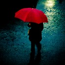 Woman with red umbrella in the rain in winter.