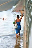 Woman walking along flooded street in Rio Branco, Acre, Brazil. February 2012.