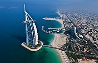 Worlds only 7 star hotel in Dubai UAE called the Burj Al Arab from helicopter above aerial with luxury and water at beach in United Arab Emirates.