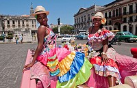 Havana Cuba local women with flowers at Capital in pink Classic Ford auto and hats smiling for tourists.