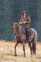 Female wrangler cowgirl on horse, Montana, USA