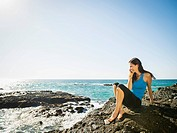 Mixed race woman smiling on rocky beach