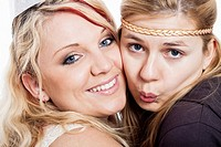 Closeup of two young blond happy girlfriends.