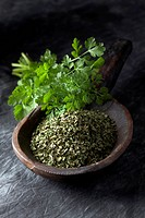 Wooden spoon with coriander on textile, close up