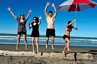 People enjoy the sea and sand at a beach in Christchurch, New Zealand.
