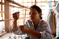 A women works in a small village textile factory outside of Phnom Penh, Cambodia.