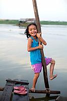 A young girl plays by the river in a small village outside of Phnom Penh, Cambodia.