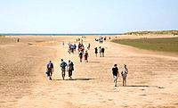 People walking across wide sandy beach at Holkham Norfolk England