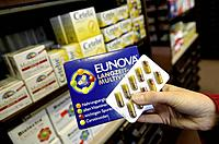 Vitamin preparations in a pharmacy. Hand holding Eunova capsules with longtime-vitamins. - BONN, GERMANY, 21/11/2003