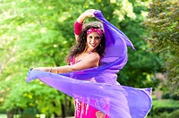 A 23 year old brunette woman in costume belly dancing outdoors.