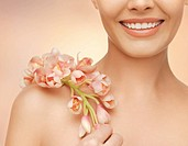 closeup picture of woman's shoulder and hands holding orchid flower