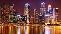 aerial view of the Central Business District by night. In the foreground the water of Marina bay. Singapore.