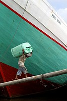 Man carrying goods on his back to load a cargo ship, Sunda Kelapa, Jakarta, Indonesia, Southeast Asia.