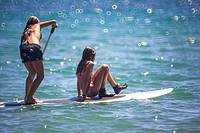 Girls on surfboard paddling in the Mediterranean Sea, Benicassim, Castellon province, Comunidad Valenciana, Spain