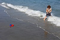 A 7 year old boy playing with a toy boat on a string in the waves at a beach at the sea