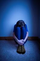 Sad girl with her head between her knees.