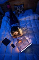 Teenage girl lying on a bed at night working on a laptop computer.