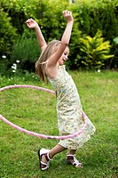 Smiling little girl playing with hula hoop in her garden.