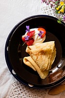 Pancakes with cut strawberries and cream on black plate on table covered with white napkin.