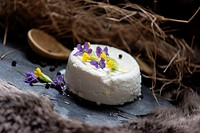 Goat cheese decorated with spring flowers and black pepper with olive oil.