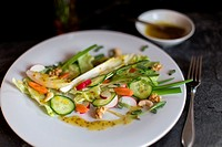Salad of spring vegetables on white plate with mustard sauce.