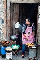 A woman cooking food for sale to tourists in Hongcun heritage village in Huizhou region, Anhui.