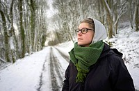 Young woman in the snow on winter day wearing glasses, scarf, and winter jacket.